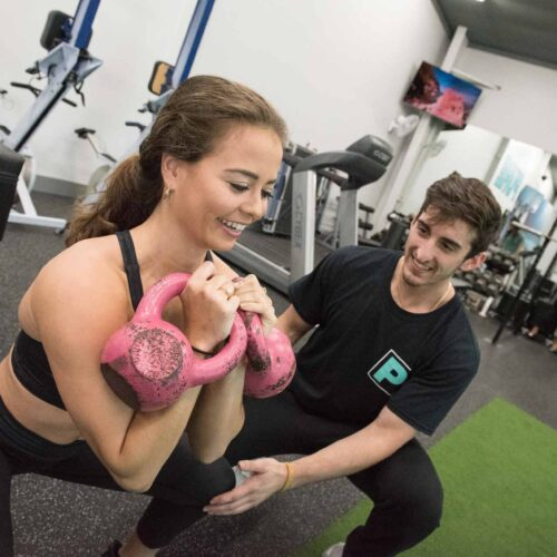 PURE Strength and Movement Woman Squatting with Personal Trainer