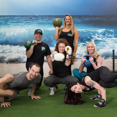 PURE Strength and Movement Team posing in front of ocean wall in Tampa